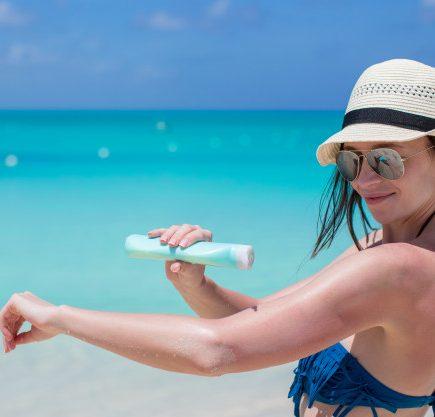 Kvinde tager solcreme på