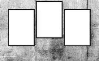 En rå væg med tre billedrammer